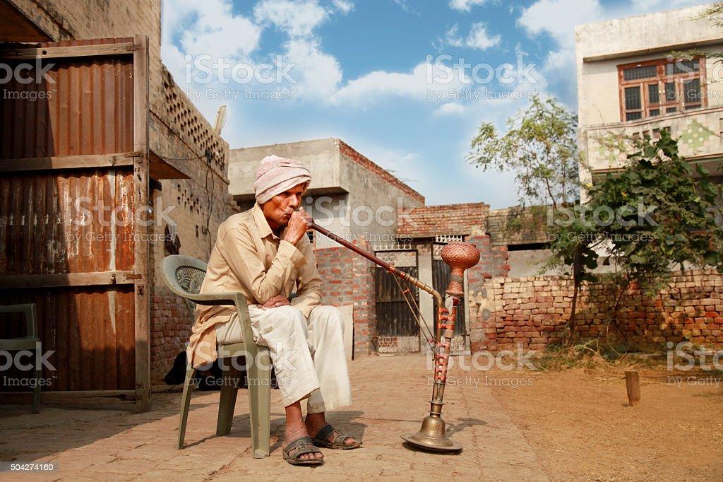 Fifty something man enjoying hookah ! stock photo