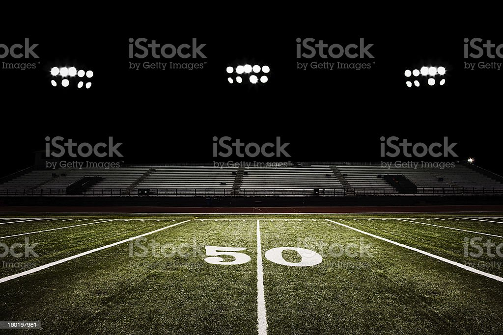 Fifty-yard line of football field at night stock photo