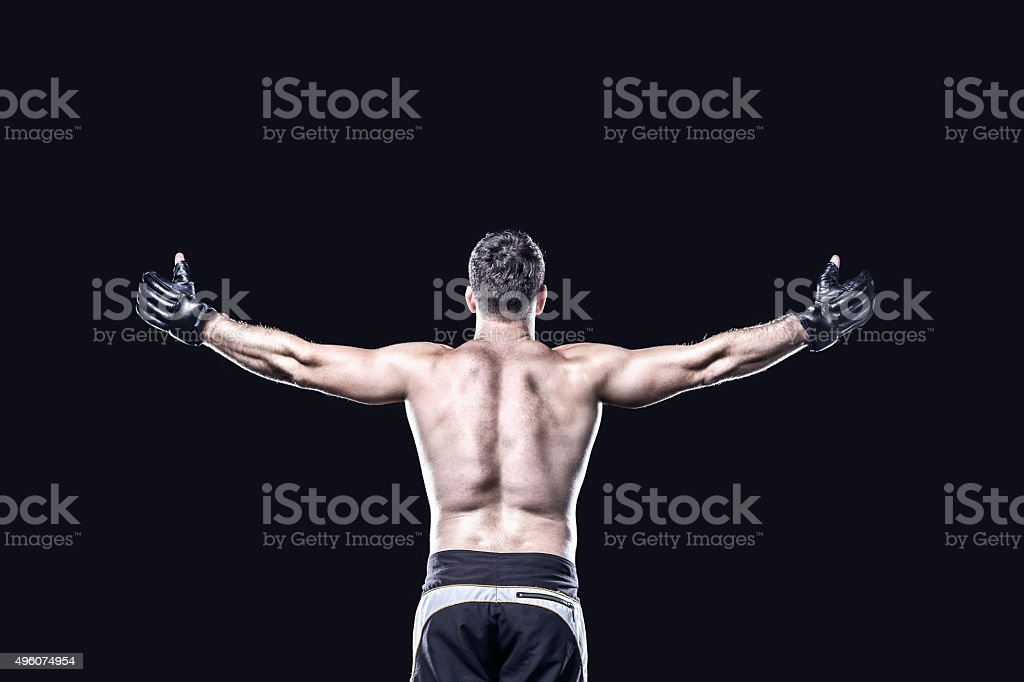 MMA fighter in celebrating victory, behind view, isolated stock photo