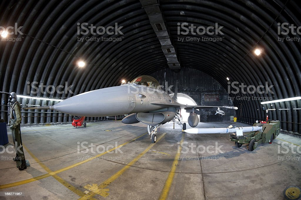 F16 Fighter in military hangar stock photo