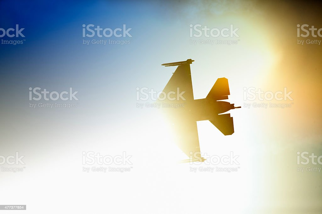 F16 fighter jet against blue sky. stock photo