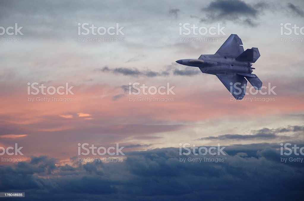 A F22 fighter jet flying through clouds in a colorful sky stock photo