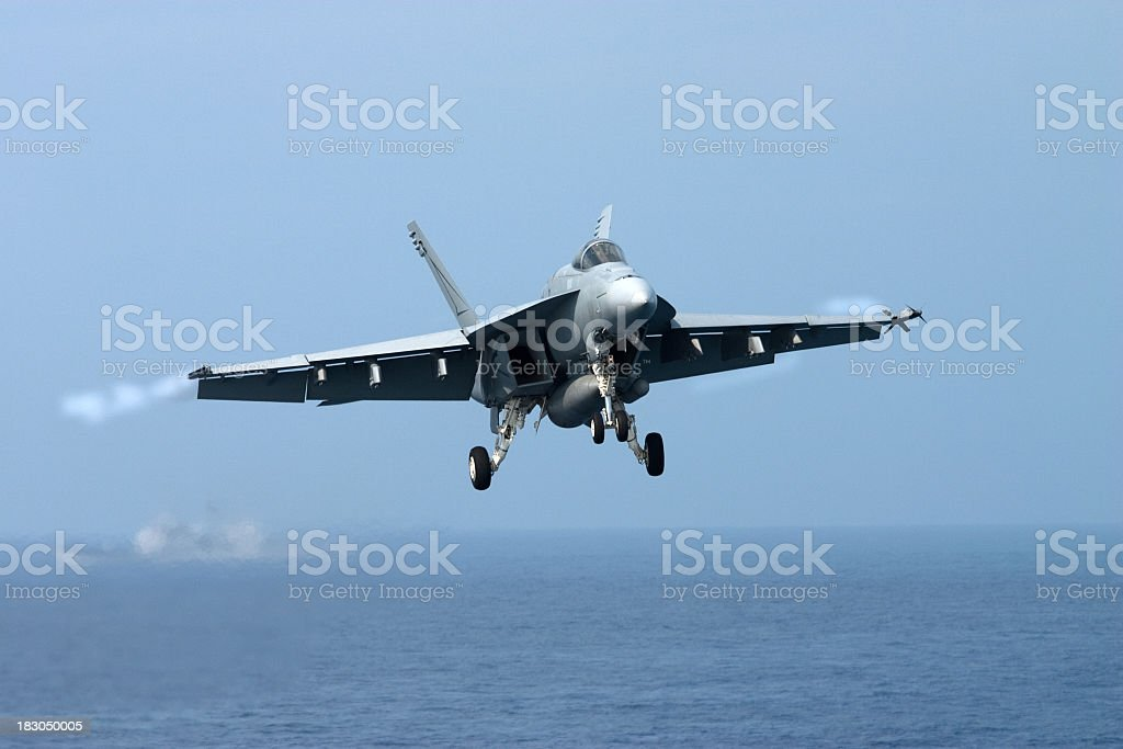 A fighter jet in the air over the sea stock photo