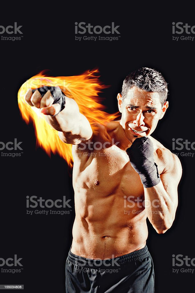 Fighter throwing a punch with fire royalty-free stock photo