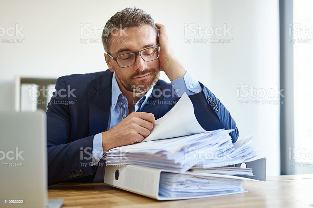 Fighting a losing battle against paperwork stock photo