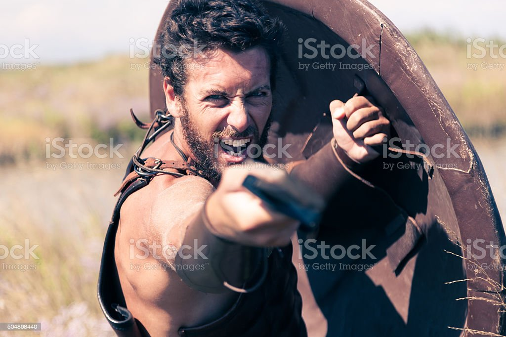 Fighting ancient warrior in armor with sword and shield stock photo