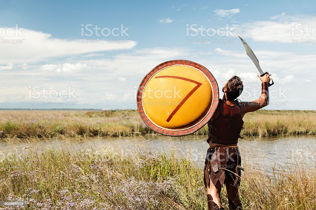 Fighting ancient warrior in landscape background stock photo