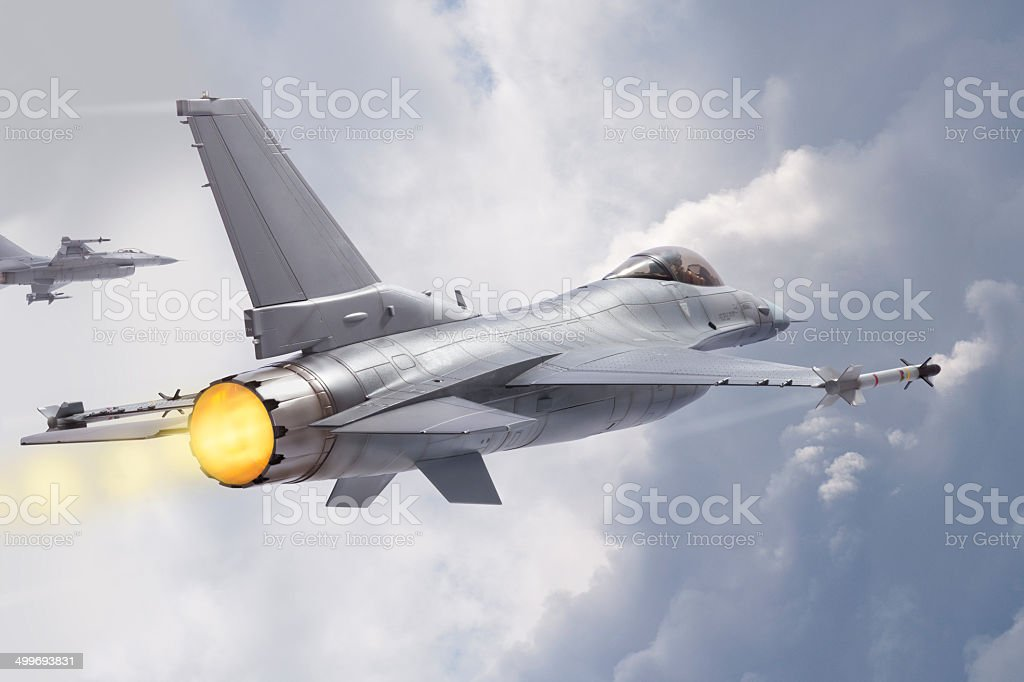 F-16 Fighting Falcon jets fly through clouds stock photo