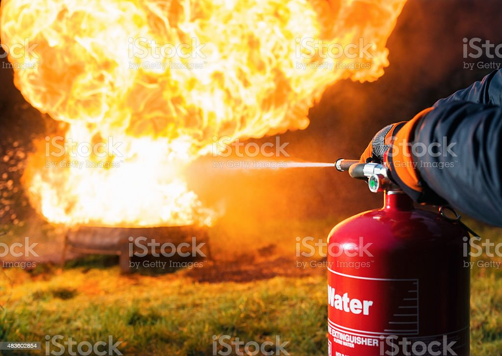 Fighting fire with a water extinguisher stock photo