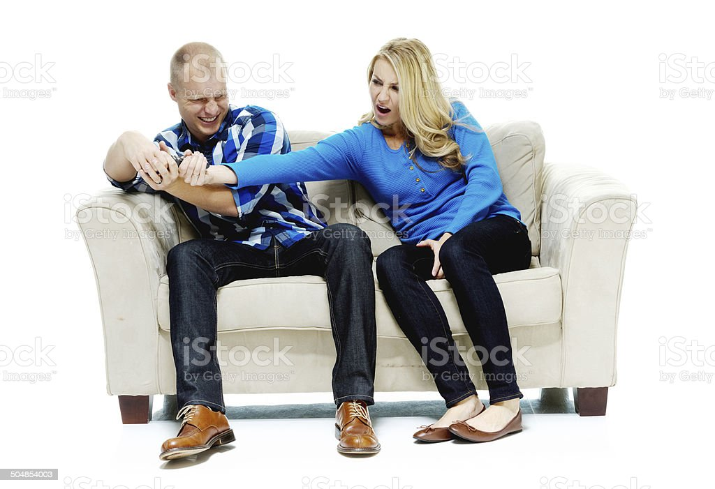 Fighting over the tv remote control stock photo