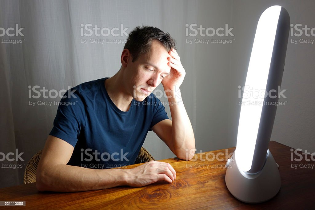 Fighting winter depression with a daylight therapy lamp stock photo