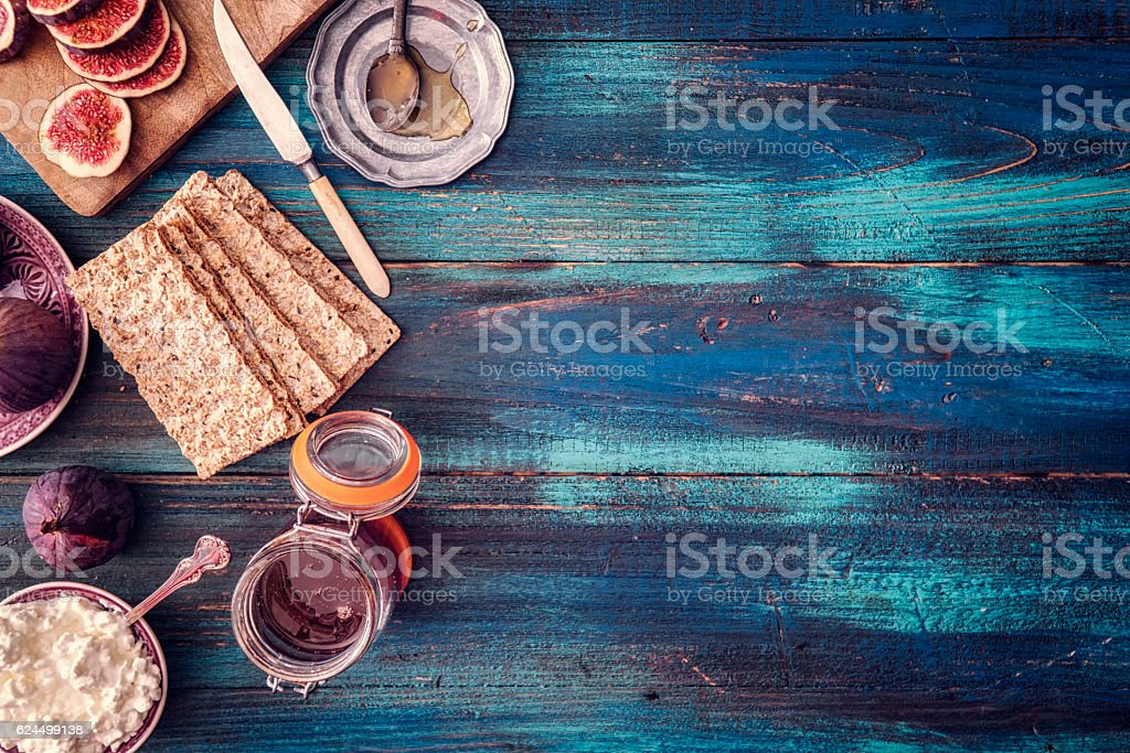 Figs, Crispbread, Cottage Cheese and Sweet Honey on Wooden Background stock photo