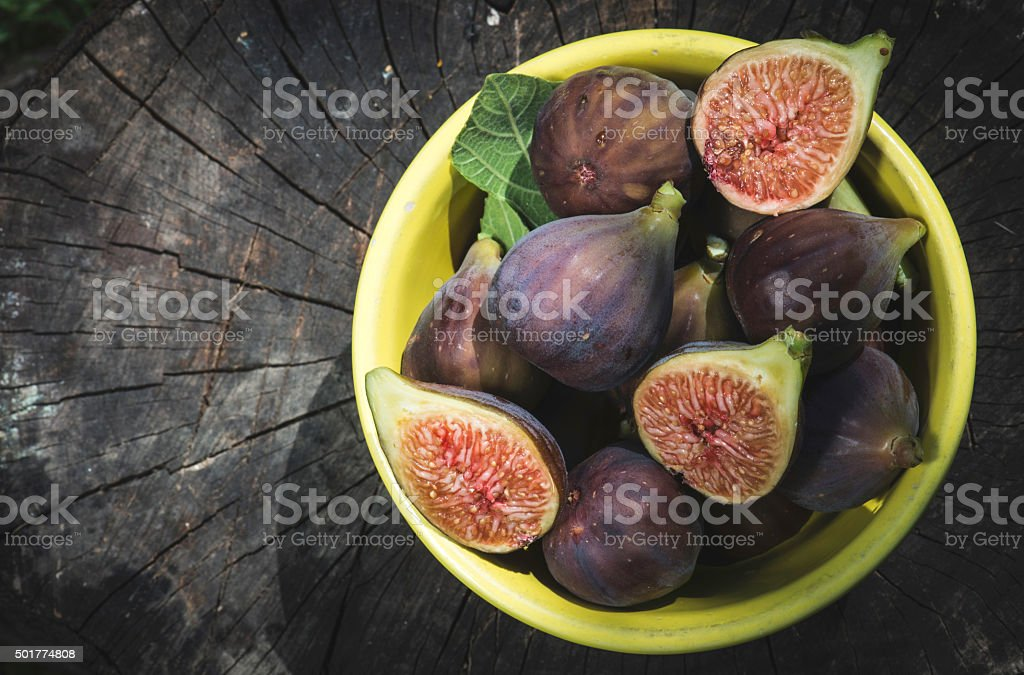 Figs in bowl on wood stock photo
