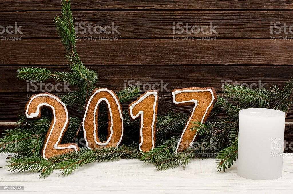 Figure in 2017 of gingerbread. Spruce branches and wooden walls stock photo