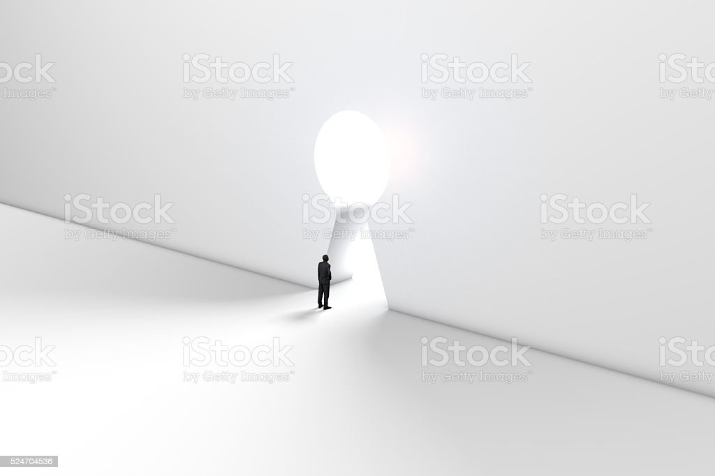 Figure in front of a bright keyhole opening stock photo