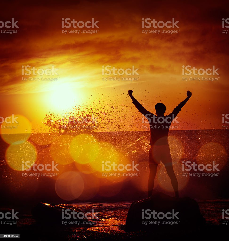 Figure of Man at Stormy Sea over Dramatic Sunset stock photo