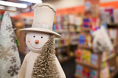 figure of snowman in hat holding christmas tree