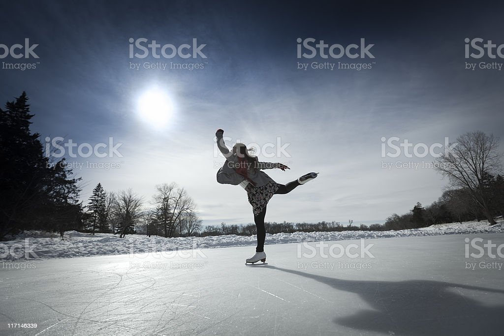 Figure Skater Skating Against Sun on Winter Pond Ice Rink stock photo