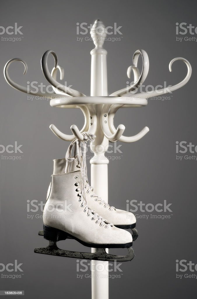 Figure skates hanging from a bent wood hatstand stock photo