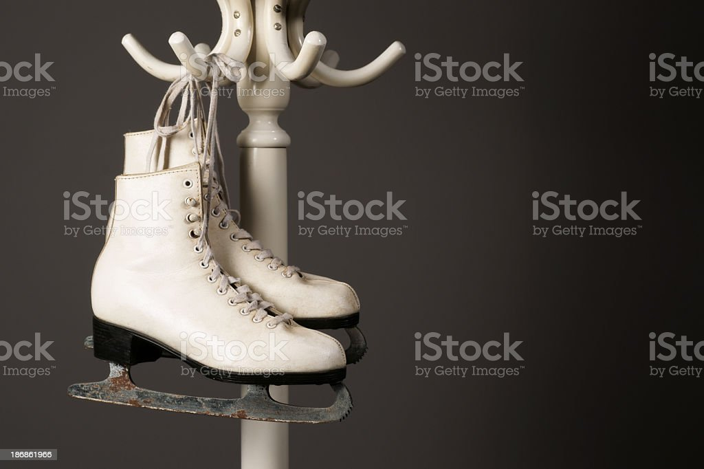 Figure skates hanging from a bent wood hatstand. stock photo