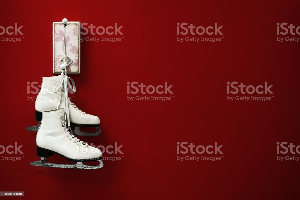 Figure skates hanging from a coat peg. stock photo