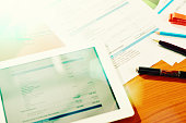 Figures and financial statements on tablet with  printouts on desk