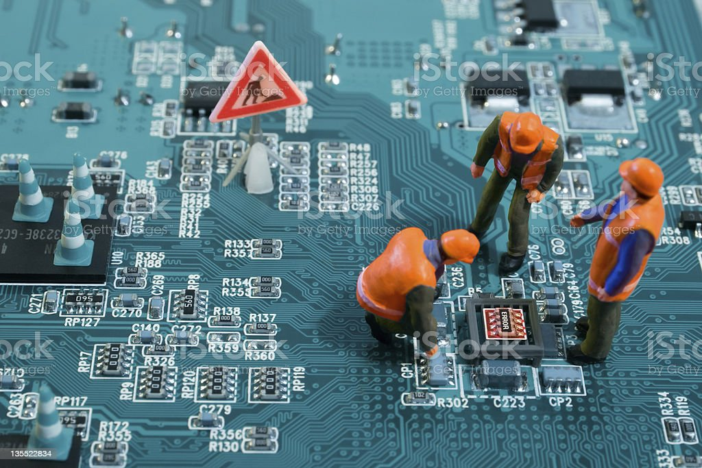 Figures of humans stand and squat on a motherboard royalty-free stock photo