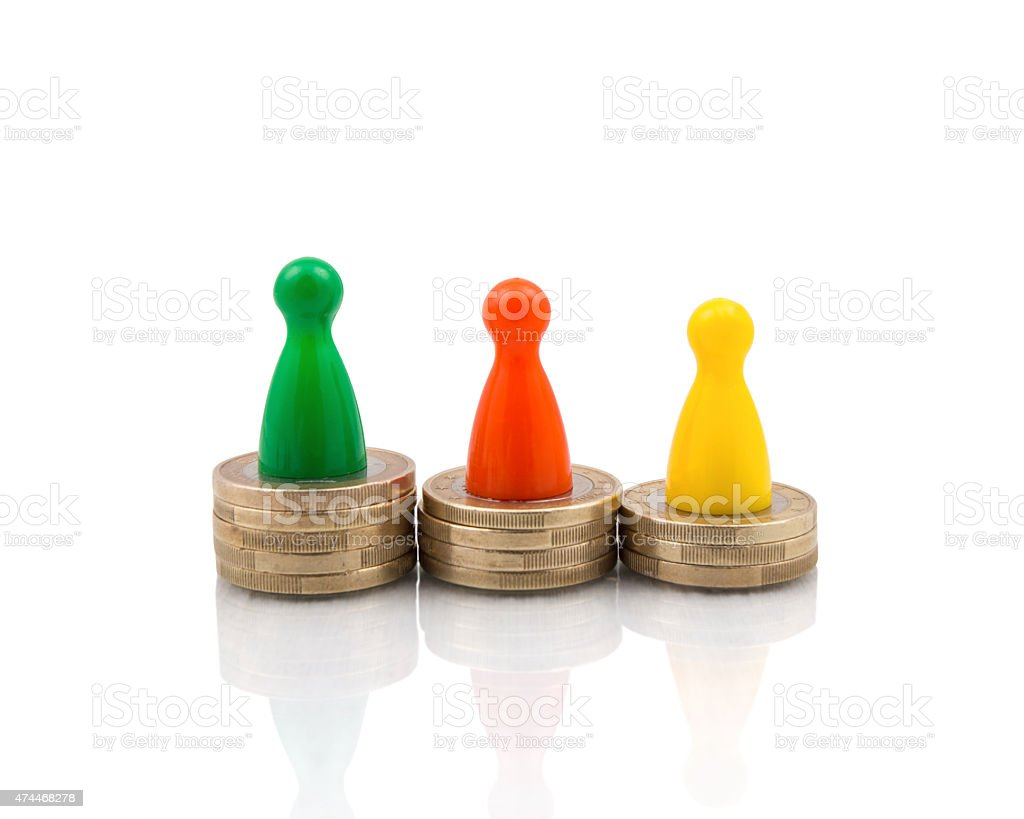 Figures on different coin stacks stock photo