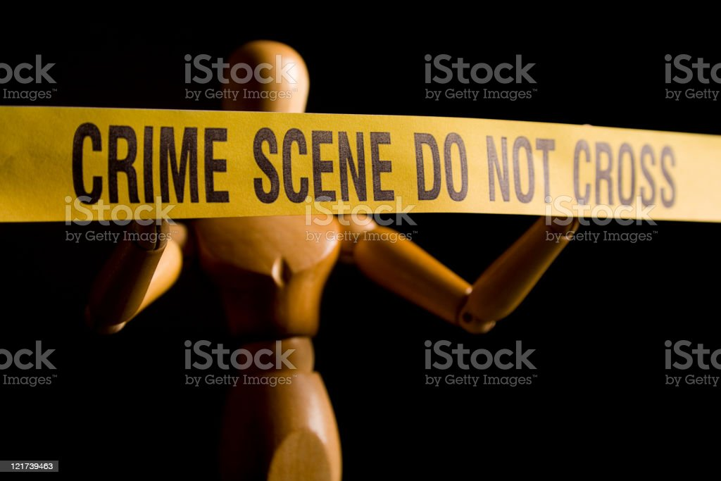 Figurine Behind Crime Scene Tape royalty-free stock photo
