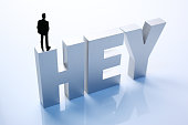 Figurine Businessman Standing on Big Letters HEY