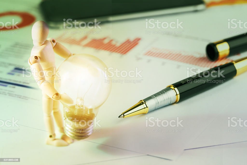 figurine concept holding the bulb with light stock photo