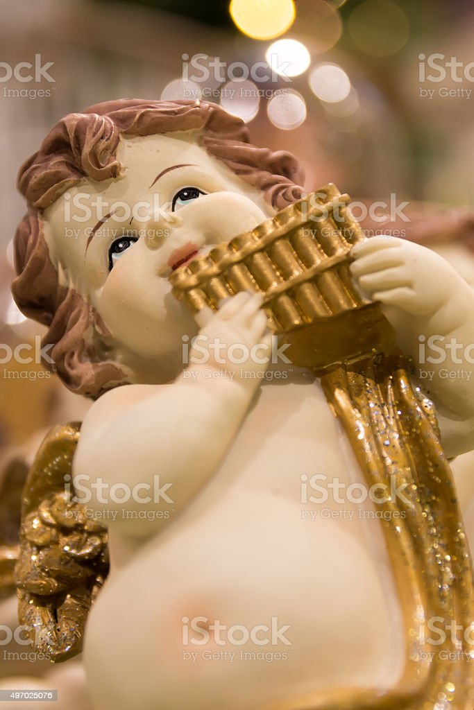 Figurine of little angel with panpipe. stock photo