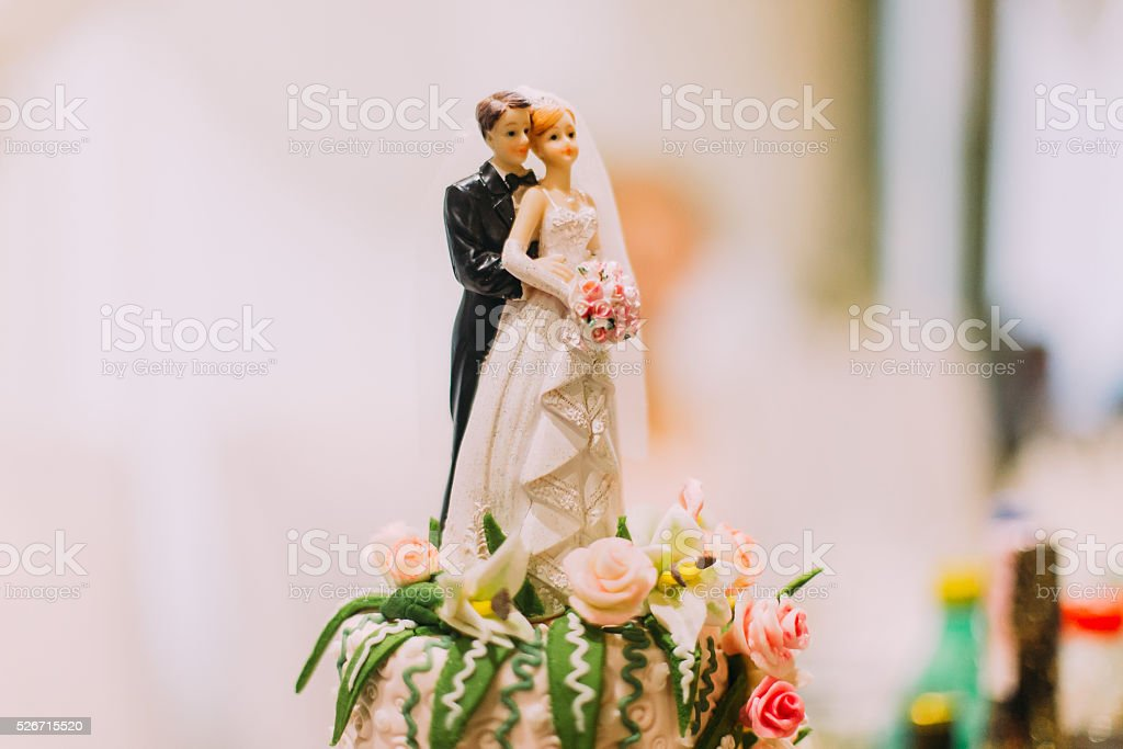 Figurines of the bride and groom on wedding cake stock photo