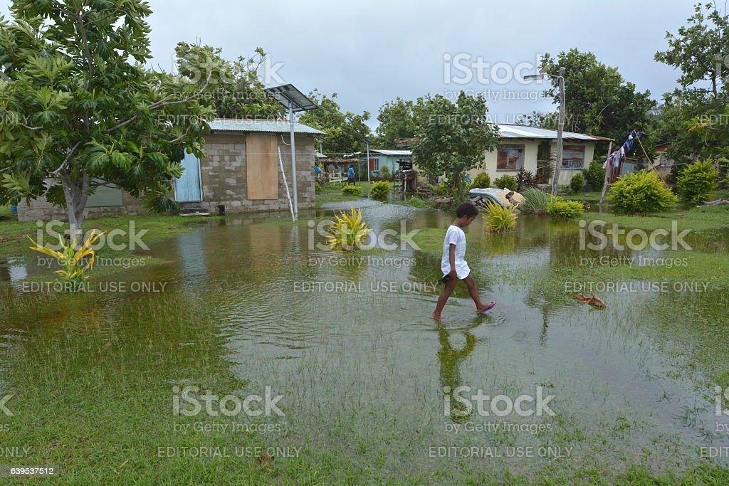 Fijian girl walks over flooded land in Fiji stock photo