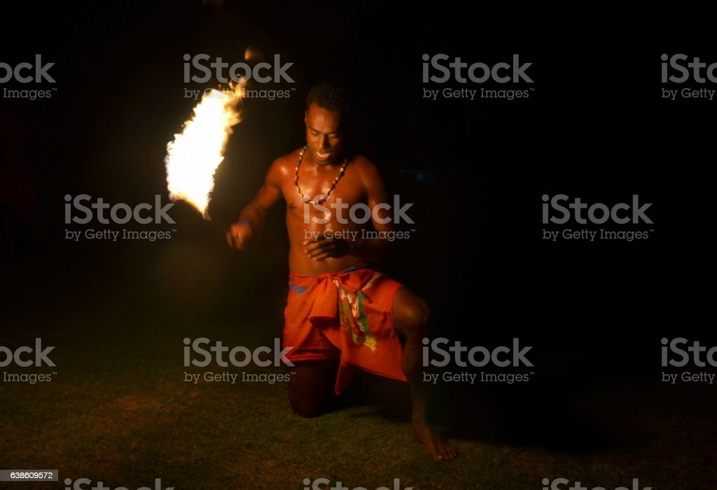Fijian man holds stick during a fire dance stock photo
