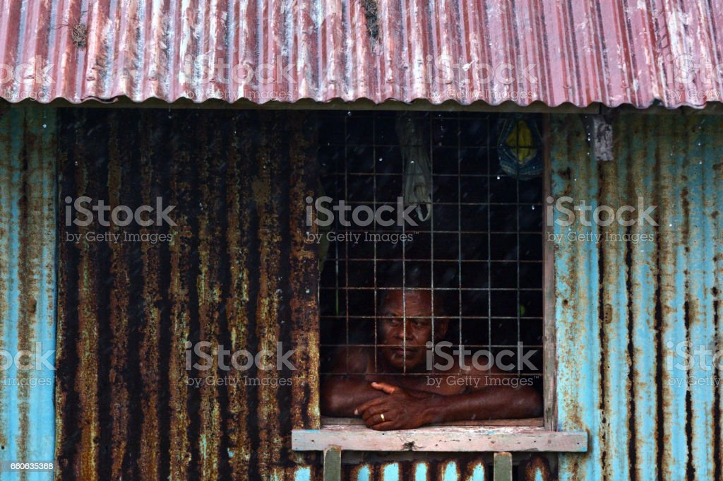 Fijian man looks out of the window during a Tropical Cyclone stock photo