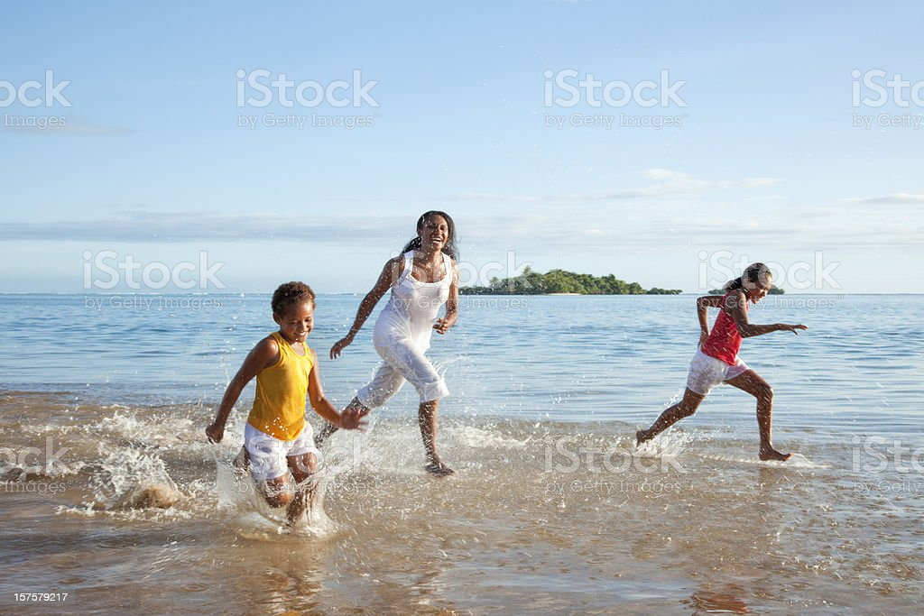 Fijian Mother and Daughters Running on Beach stock photo