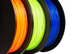Filament for 3d printing. Orange, green, blue colors. Isolated, cutout.