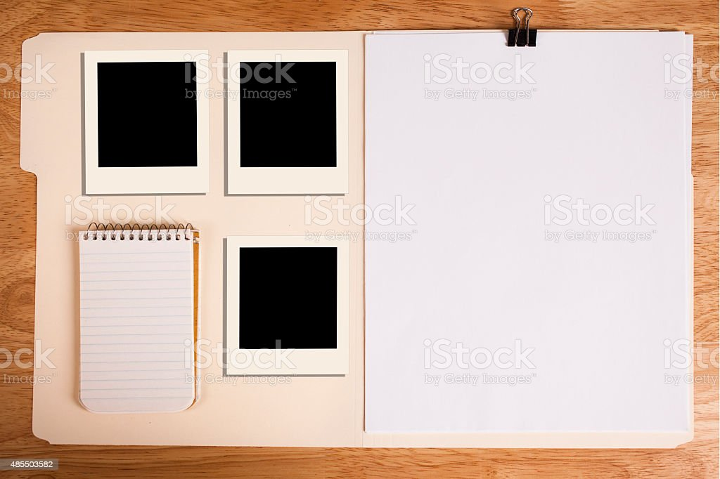 File folder with blank papers on desk, polaroid-style photos, notepad. stock photo