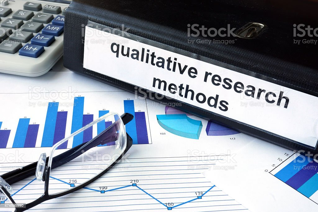 File folder with words   qualitative research methods and financial graphs. stock photo