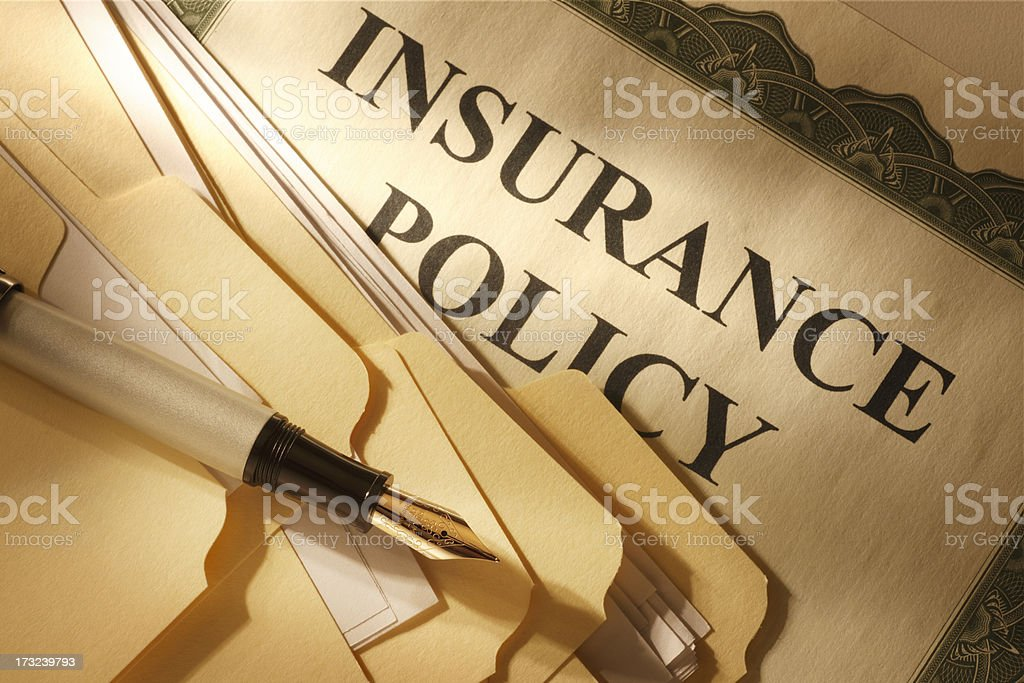File folders and fountain pen resting on insurance policy royalty-free stock photo