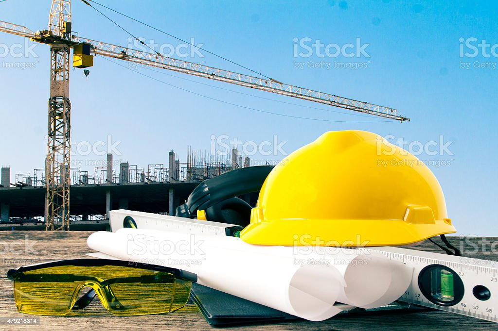 file of safety helmet and architect plant on wood table stock photo