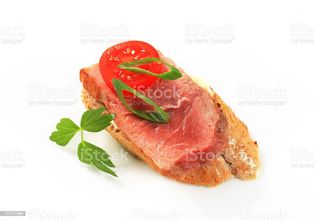 Filet mignon on a slice of baguette royalty-free stock photo