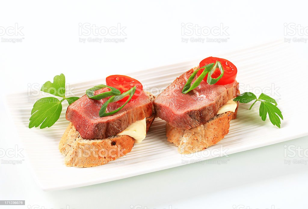 Filet mignon on slices of baguette royalty-free stock photo