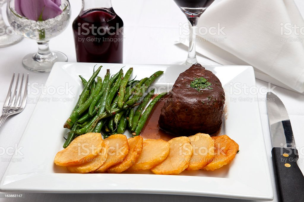Filet Mignon with potatoes and string beans, in elegant setting royalty-free stock photo