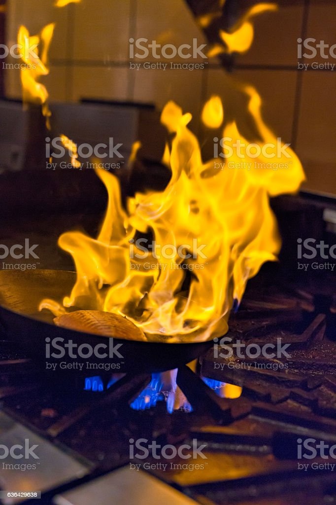 Filet of salmon in a flaming skillet stock photo