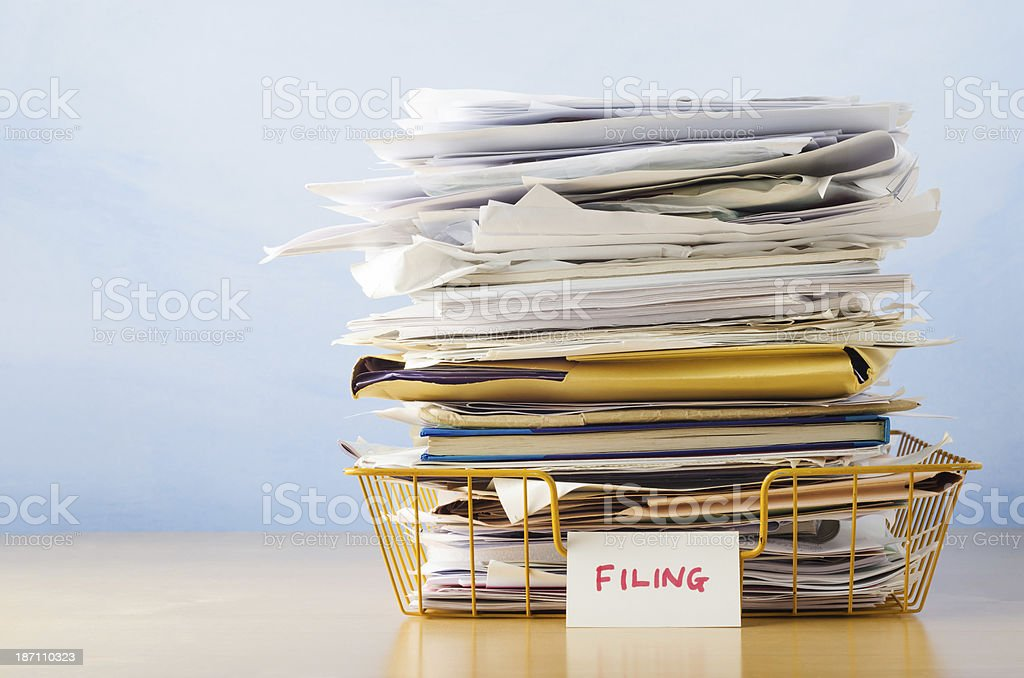 Filing Tray Piled High with Documents stock photo