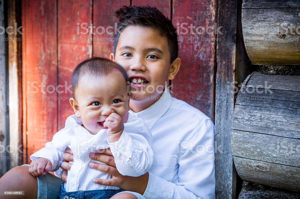 Filipino boy holding baby brother outside. stock photo