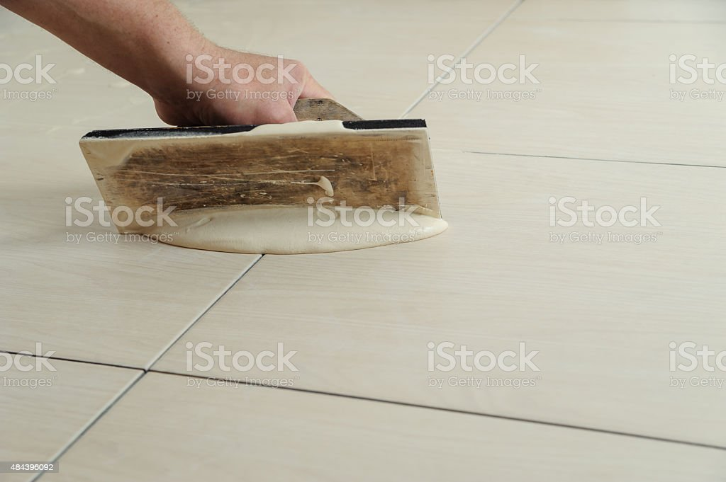 Fill the tile joints with grout stock photo