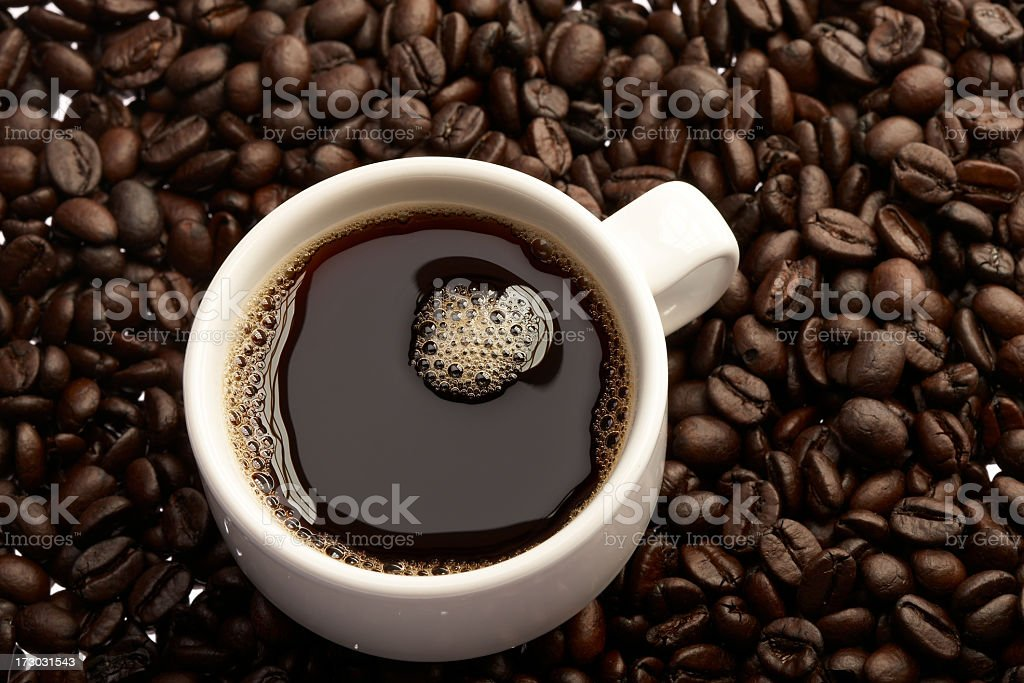 Fill white coffee cup on top of coffee beans royalty-free stock photo